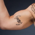 Baron Has some alphabet tattoos in his right arm image.